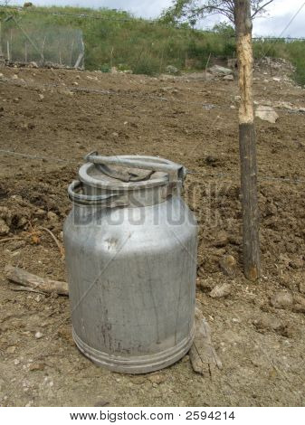 Milk Can Near A Fence