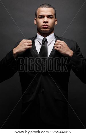 Young handsome African-American businessman in black suit.