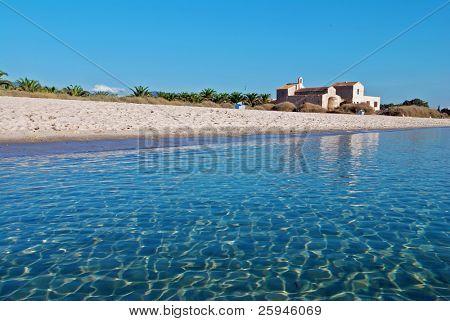 Nice white beach with blue sea and a church on Sardinia