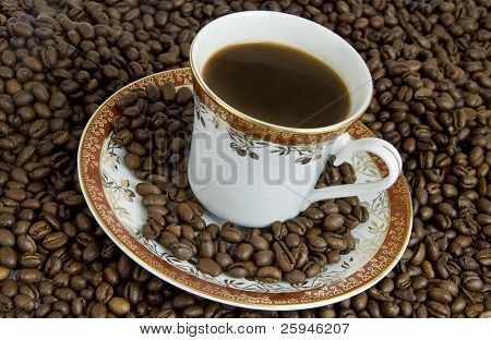 Hot drink of coffee with saucer and beans