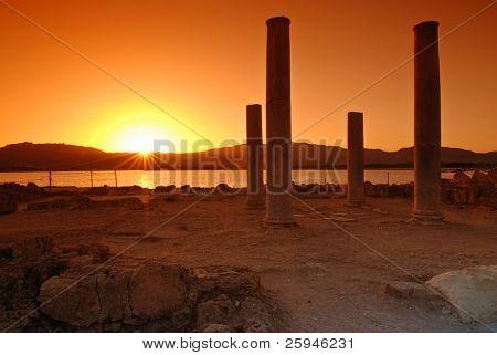 Puesta de sol y pilares de ruinas en la ciudad sarda de Nora