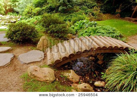 Japanese garden with many flower species and a wooden bridge