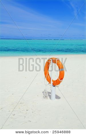Orange lifebuoy on the beautiful white tropical beach