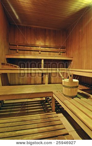 Empty wooden sauna with a bucket of water