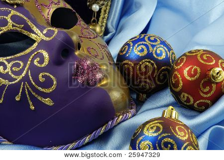 Beautiful Venetian Mask is laying on a blue velvet with decorative balls