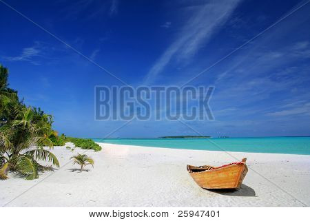 Tropical Maldivian beach with palms and wooden fishing ship