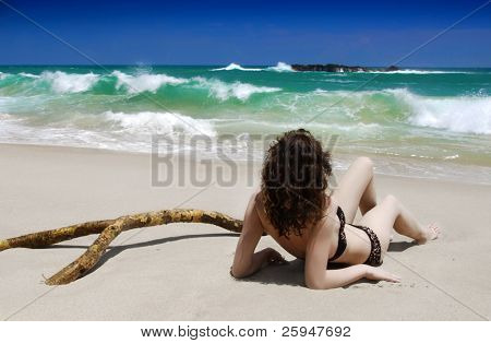 Beautiful young brunette is laying on the beach of the tropical sea with palm branch and watching waves