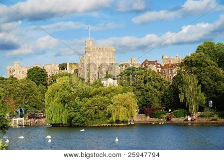 Panorama of the mighty Windsor castle, the home of the Queen, with the river Thames and boat trips docks in the foreground
