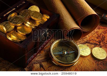 Old brass compass lying on a very old map with treasure chest full of golden coins