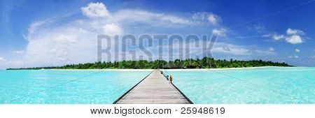 Tropical Maldivian paradise - a jetty leading to a beautiful tropical atoll hiden in the azure Indian ocean. Wide panoramic photograph.