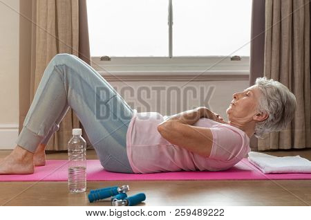poster of Senior woman doing sit ups on yoga mat at home. Fit healthy old woman doing abdomen crunches at home