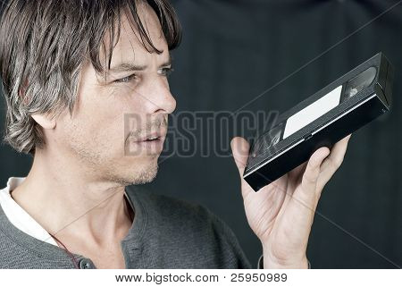 Man Looks At Video Tape In Confusion