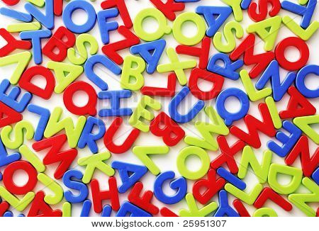 Plastic colorful random letters on white background.