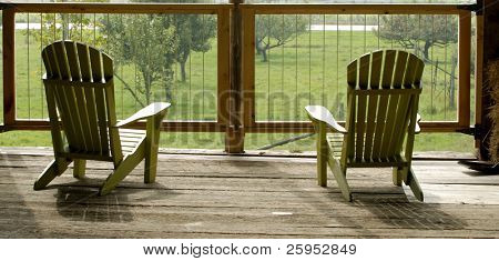 Two Muskoka Wooden Chairs In An Old Barn Overlooking An Orchard