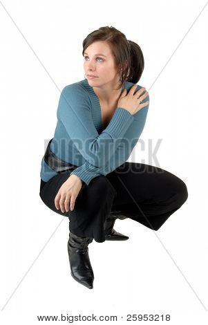 Young Woman Crouching Down, Dressed Casually Isolated On A White Background