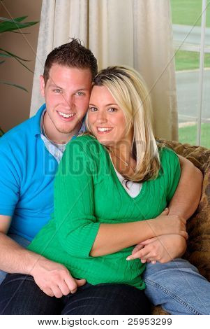 Young Couple In Love Sat Together On A Sofa At Home