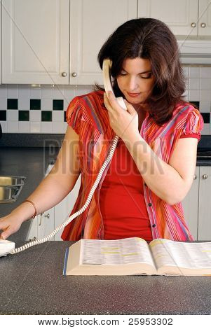 Brunette Woman Dialing A Phone Number From The Telephone Directory