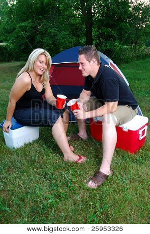 Young Happy Couple Relaxing In Front Of Their Tent Sat On Coolers
