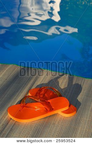 Flip Flop Thongs On A Bamboo Mat By The Edge Of A Swimming Pool