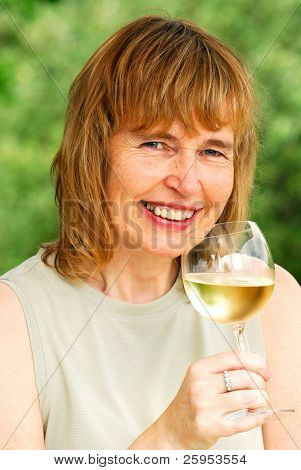 Female Baby Boomer Enjoying A Glass Of Wine Outdoors In The Summertime