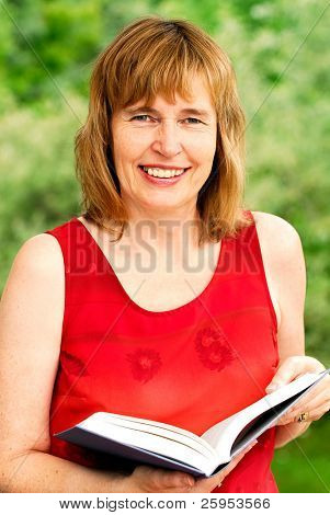 Attractive Middle Age Woman Reading A Book Outdoors In Summertime