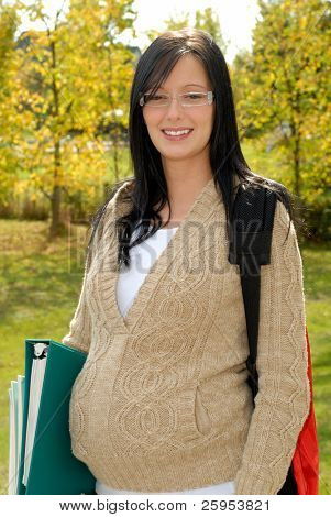 Beautiful Pregnant Brunette Teen Girl Expecting Her First Baby, Outdoors Ready For Back To School