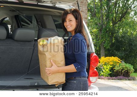Young Woman Loading Her Groceries Into The Trunk Of An Sport Utility Vehicle
