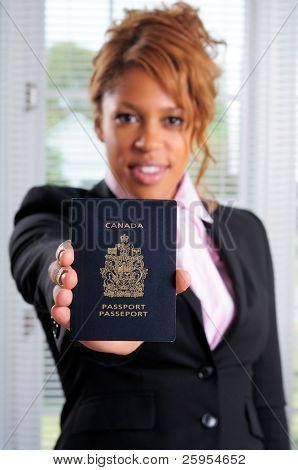 Pretty African American Businesswoman Holding Her Canadian Passport, Shallow Focus On Passport