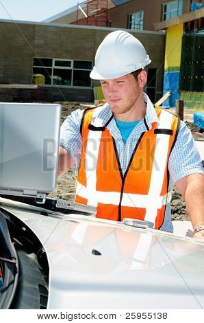 Architect On Site Using A Computer And Mobile Cellphone To Keep Connected