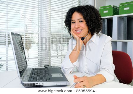 Call Center Woman Wearing A Telephone Headset At Her Desk In The Office