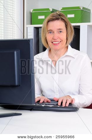 A Middle Age Woman Working With A Computer In Her Office