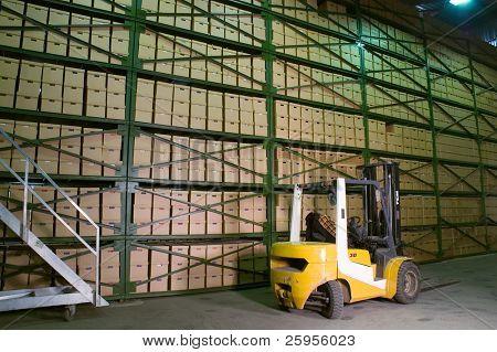 Truck in het magazijn. Vakken op de planken in de achtergrond.