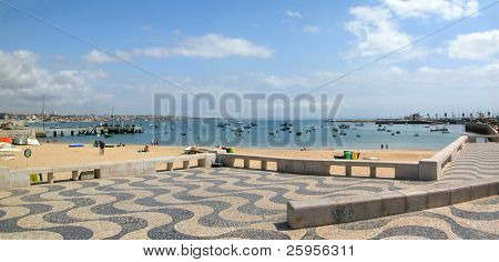 Cascais bay - summer resort in Portugal. A lot of boats in the bay, sandy beach, beautiful sky, wavy pavement in foreground.