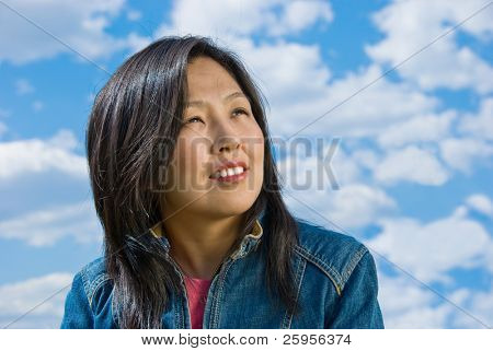 Attractive young woman portrait over sky background with room for text