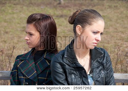 Quarrel girls sit on a bench in a park