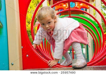 kleines Mädchen spielt im Spielplatz in einem park