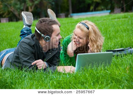 Young couple relax and listen to music from laptop on the grass in the park