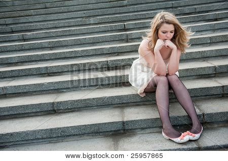 Sad lonely girl sitting on the steps