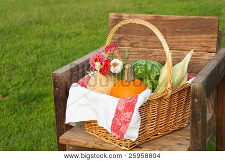 Harvest basket with produce and flowers on a rustic chair