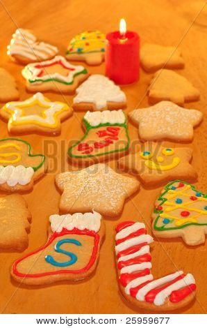 Santa's own cookies marked with an S, surrounded by colorful homemade Christmas cookies on a wooden table with a candle