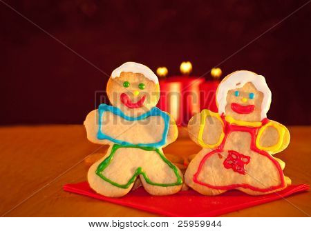 Two Christmas cookies holding hands, standing on a red napkin with three candles with hearts for flames on background