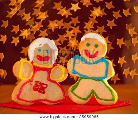Two funny, colorful Christmas cookies shaped like a girl and a boy standing on a red napkin, holding hands against starry light background