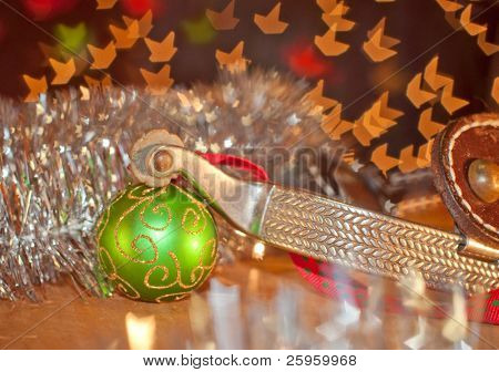 Western cowboy Christmas - spur and a green ball ornament on silver tinsel with starry light background