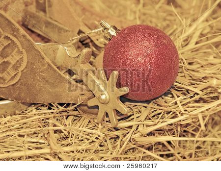 Cowboy Christmas - old spurs on hay with a red ball ornament in muted sepia tone