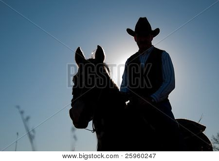 Man and horse silhouetted against sun