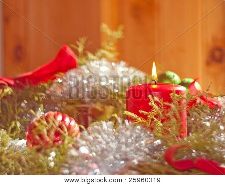 Christmas candle burning inside a wreath with heart bokeh reflecting off shiny tinsel and ornaments