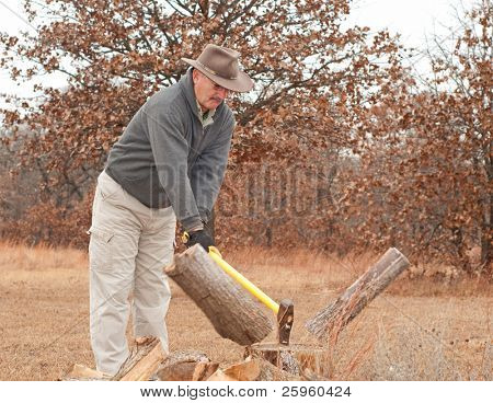 Middle-aged man chopping fire wood with an ax on a cold late fall day