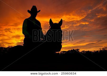 Silhouette of a horse and a rider in a cowboy hat against late evening storm clouds