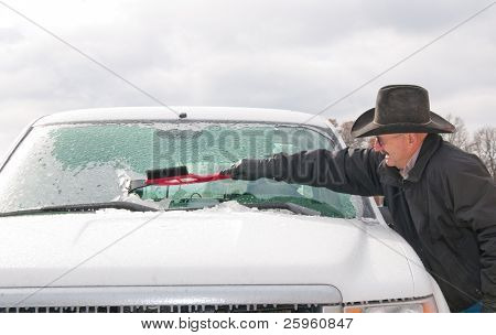 Middle-aged man scraping ice off his vehicle windshield on a cold winter morning after an ice storm