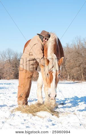 Man hugging a big Belgian Draft horse, bundled up in heavy winter clothes on a bitter cold winter day